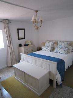 The bedroom is comfortably furnished with a king size bed