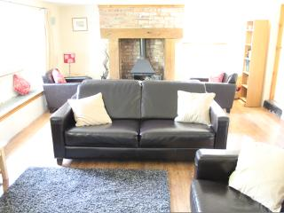 Living room with wood burning stove. large sofas and wide screen Sky+ TV