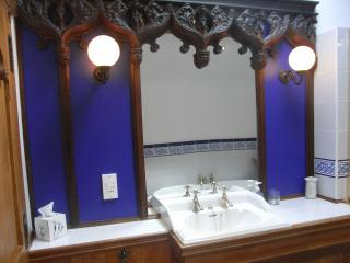 Old reclaimed church carvings surround mirror above the basin.