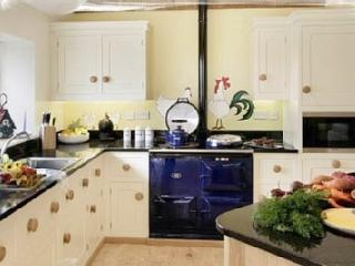 Large Mark Wilkinson Cooks kitchen with blue aga stove, crystal ware and fine crockery