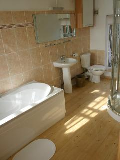 Large ensuite off bedroom, including bath and shower - wood flooring