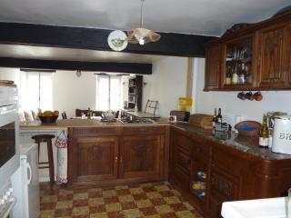 Kitchen area with lounge beyond breakfast bar,modern equipment housed in old french furniture
