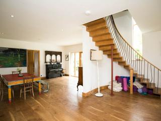 Beautiful wooden stairs leading up from the open planned sitting/dining room