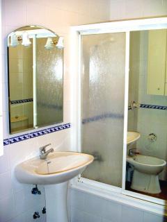 Baño completo. Bañera con mampara, bidet y lavabo.