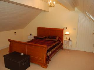 Master bedroom with clock radio & sleigh-bed. Also hair dryer.
