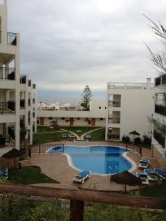 View of complex swimming pool with the sea in the background