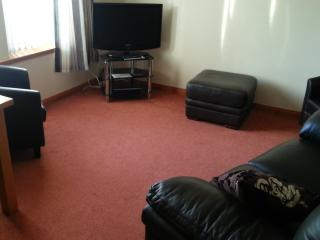 living room with wide screen tv leather sofa and two recliners