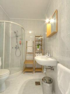 Bathroom with a roomy walk-in shower, towels, body care products, a washing machine with detergent