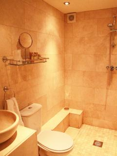 Travertine tiled wetroom with complimentary toiletries