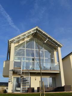 Sunny rear decking and glass walled living area letting the outside in!