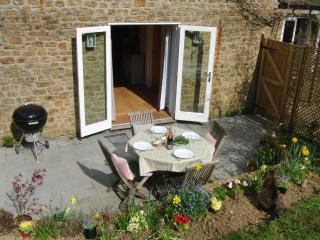 The sunny private patio, with barbecue, and sand pit or paddling pool for the children.