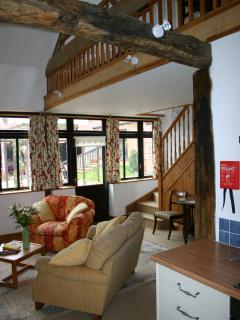 sitting room showing staircase and vaulted roof