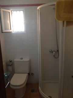 Bathroom near the kitchen, with shower plate. Natural ligth by a window.