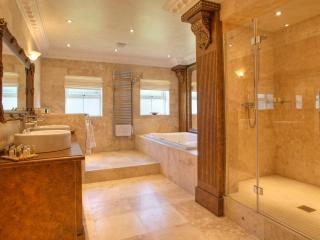 large luxurious family bathroom with large shower, his and hers sinks and double bath