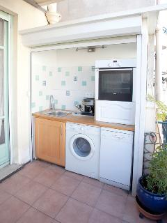 Summer kitchen on terrace with automatic washing machine dishwasher oven with rotisserie