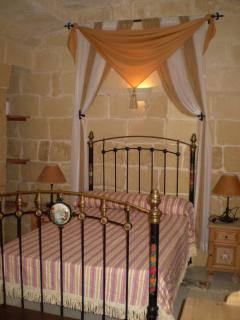 A traditional Iron Maltese Bedroom with a curtain feature in the background with ensuite shower room