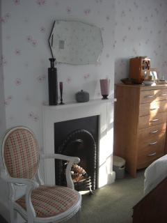 The Double Bedroom with bedstead, chest, wardrobe, fireplace, window with garden view