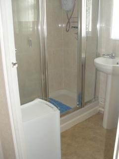 Shower room with low step for ease of access.