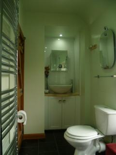 Designer vanity area with feature mirror. Stylish heated towel rail for the fluffy towels