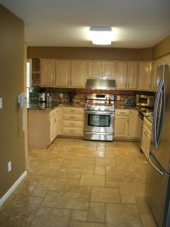 View of kitchen showing gas stove and double door fridge on right.