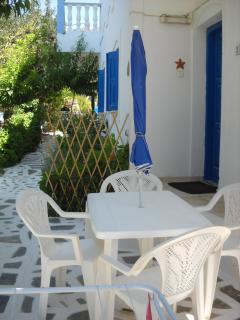 Terrazzino privato con tavolo,sedie e ombrello da sole adiacente alla piscina