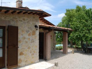 Vista frontale del casale con, in secondo piano, il giardino e la piscina.