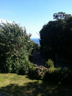 Sea view and garden from front of the house. The private, south-facing garden is a perfect sun trap