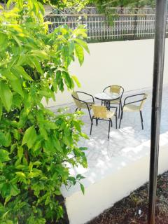 Sitting area  on the  back patio  covered  by  vines -  if the  sun  gets too much !!