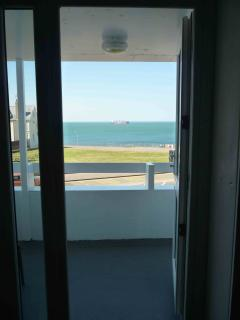 Looking from dining table to balcony, with blue sea beyond