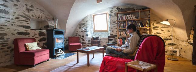 La grande salle côté salon avec son poêle à bois, sa bibliothèque, ses jeux...