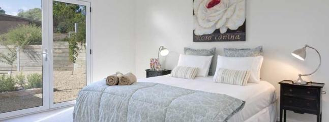 The stunning second bedroom has beautiful linen and french doors opening onto a quaint garden area.