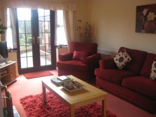 Lounge/ dining area with flat screen tv with freeview,dvd player,patio doors to rear.