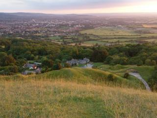 View from top of Cleeve Hill with cottage and hamlet in foreground and Bristol channel in distance