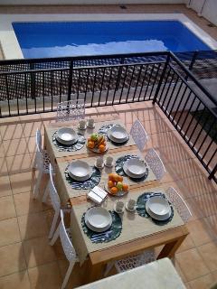 Terraza de la cocina, con vistas al jardín y a la piscina.