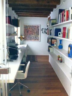 Ingresso dell'appartamento, con lunga libreria e ampio tavolo con il computer