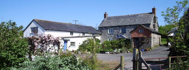 The Farmhouse and Cottage from across the farmyard (we live in the lower end of the White Cottage)