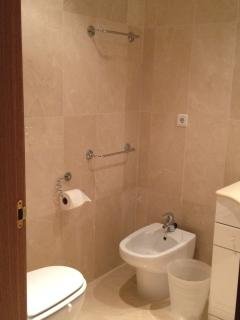 Ensuite to Bedroom 1, fully tiled, marble bathroom with bath, over shower, toilet, basin and bidet