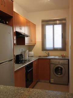 Kitchen with fridge freezer, cooker, microwave and washing machine.