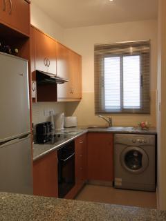 Kitchen with fridge freezer, cooker, microwave and washing machine.