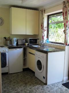 The galley kitchen, with cooker, fridge, microwave and washing machine.