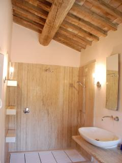 Camera Rosa ensuite: double shower set against travertine marble.