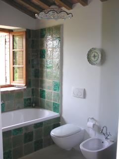 Camera Azzurra ensuite: bath with shower above, handmade tiles and Maiolica light, West-facing.