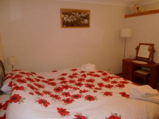 The cottage is decorated in a theme of red poppy furnishings and sheep pictures.