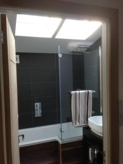 Modern bathroom with bath and monsoon LED shower, controllable heated floor and BOSE with remote