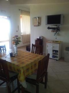 Il soggiorno con tavolo pranzo e TV piatto