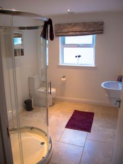 The shower room is spacious with a large D shaped shower