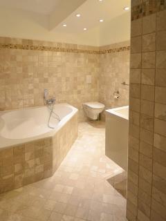 Salle de bain en marbre avec baignoire d'angle, double vasque et WC