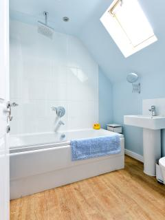 Modern bathroom with overhead shower, wall towel rail and skylight