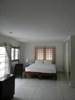 Large bedroom with work table, large balcony, windows & en-suite bathroom.