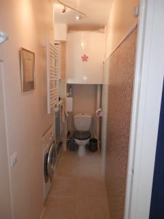 Machine à laver le linge, radiateur sèche serviettes, et les toilettes au bout du couloir ...